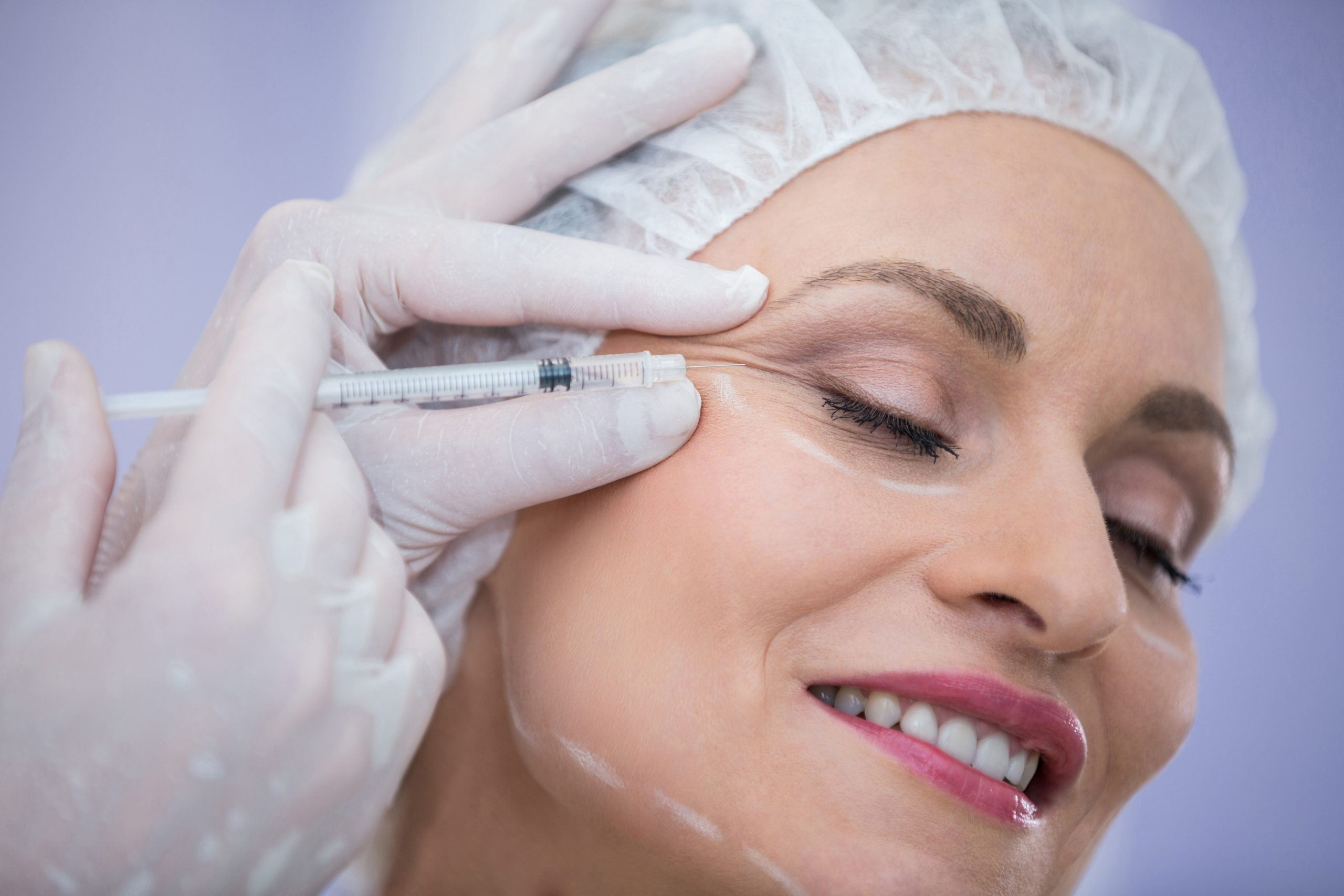 Close-up of woman receiving botox injection at clinic